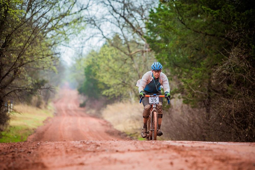 Un cycliste avec son gravel sur une chemin argileux lors d'une course