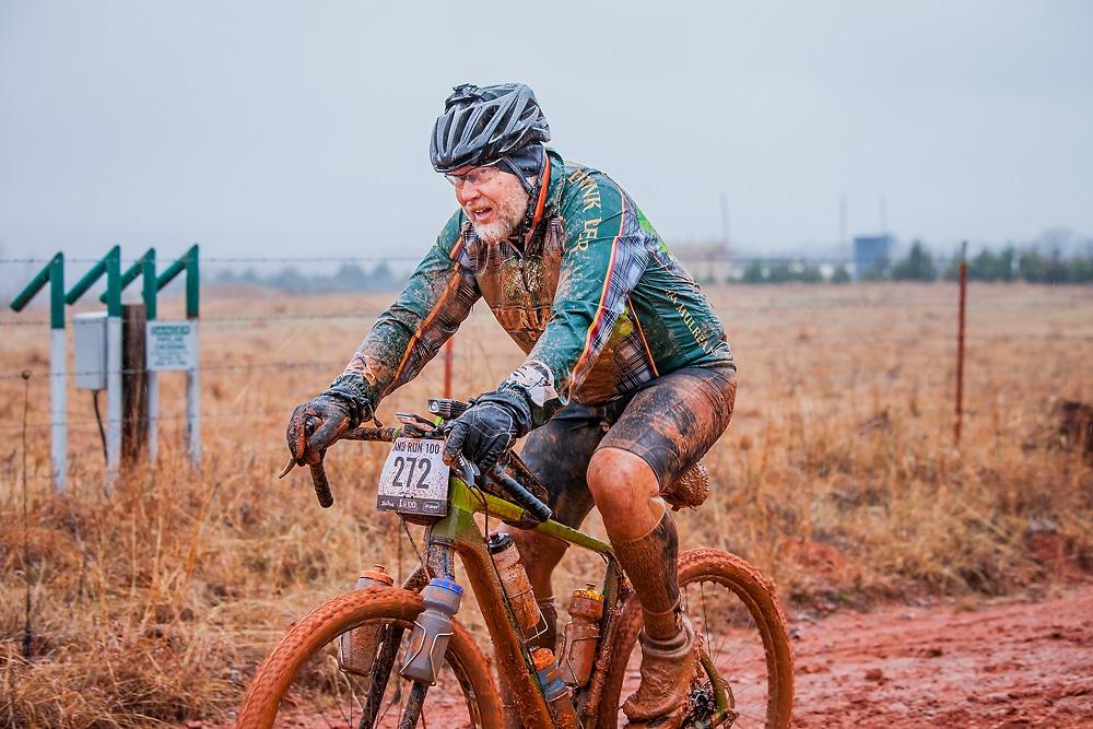 Un cycliste entièrement recouvert de boue lors d'une compétition en gravel bike