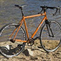 Un vélo fixie orange près de l'eau