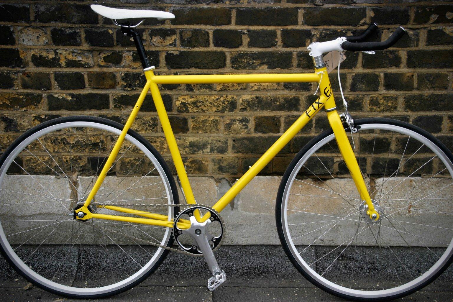 Un vélo fixe jaune posé sur un mur