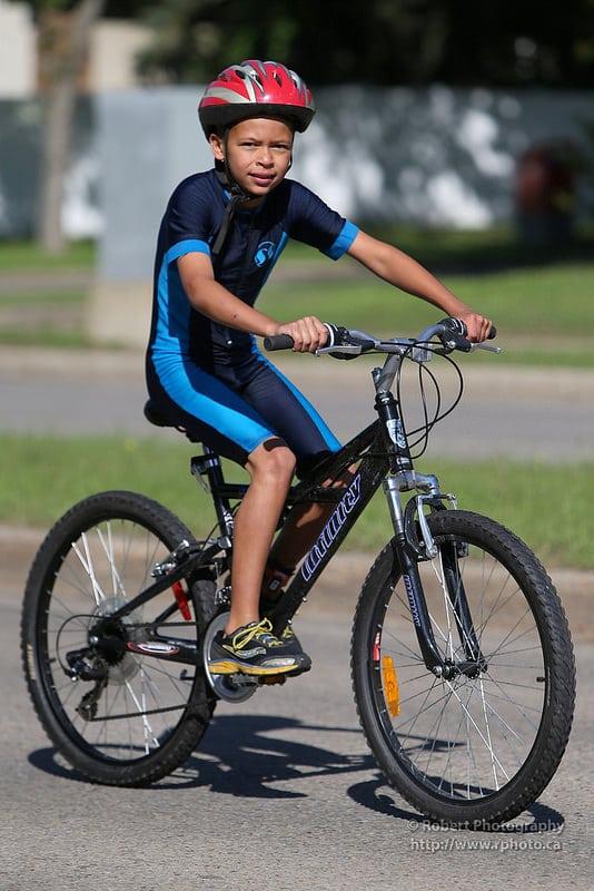 Un jeune cycliste avec un casque lors d'un triathlon