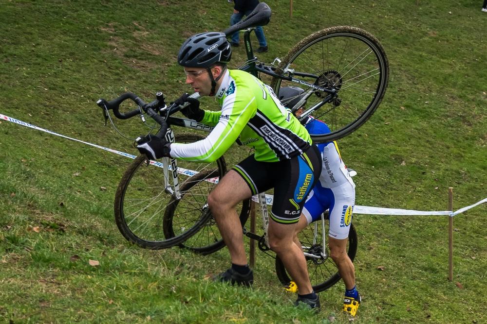 Un cycliste avec un casque qui porte son vélo lors d'une compétition de cyclocross