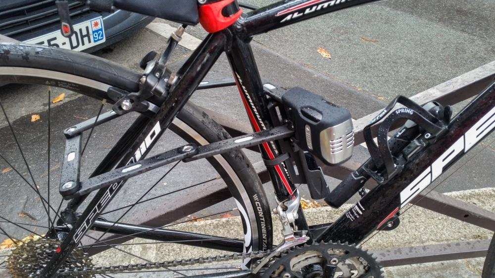 L'antivol Abus déplié avec un vélo attaché à du mobilier urbain