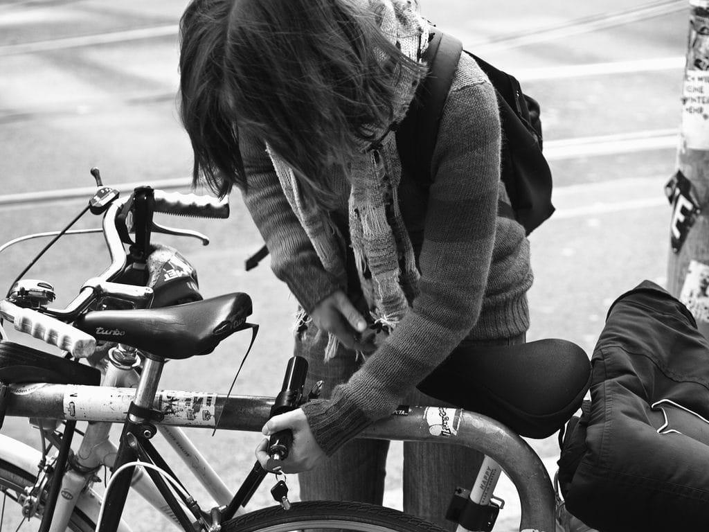 Une femme utilise un antivol pour protéger son vélo
