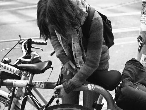 Une femme qui attache son vélo avec un antivol
