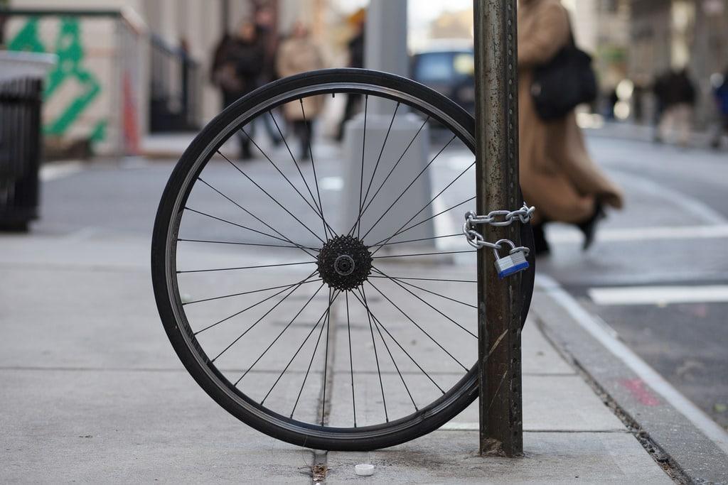 Une roue de vélo arrière attaché à un poteau avec un antivol