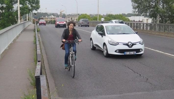 Une cycliste au bord de la route sans piste cyclable