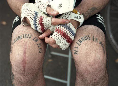Un cycliste tatoué aux genoux avec une phrase