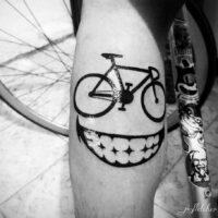 Un tatouage de vélo au mollet avec un sourire