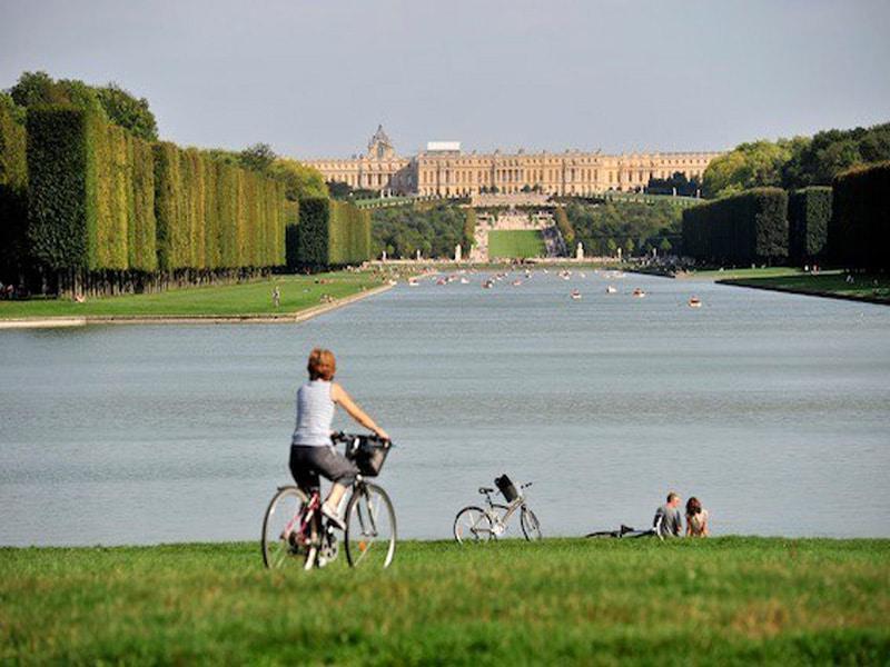 Une cycliste devant le chaâeau de Versailles