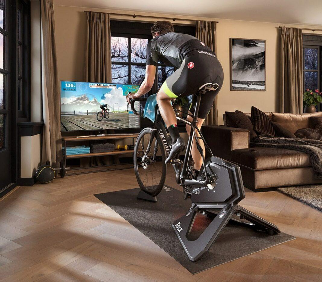 Un cycliste sur un hometrainer connecté et intéractif sous Zwift dans son salon chez lui
