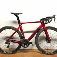 Un vélo de route rouge Factor avec une paire de roue DT Swiss ARC 1100