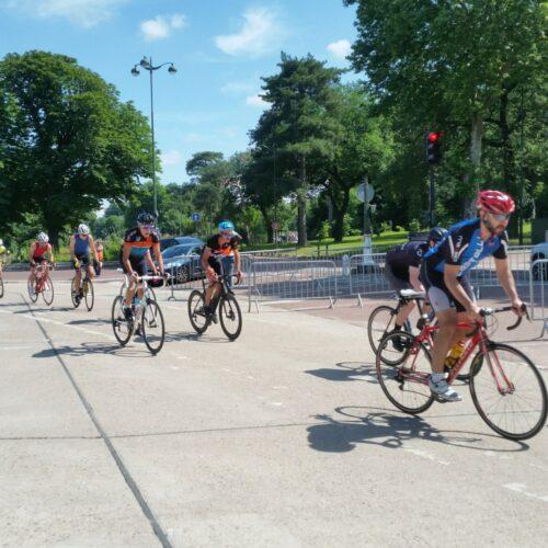 Des cyclistes qui roulent au soleil sur l'anneau de Longchamp autour de l'hippodrome