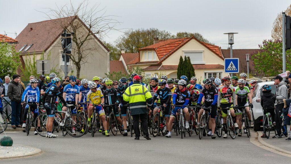 Un comissaire devant des cyclistes avant le départ d'une course FSGT