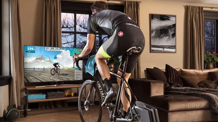 Un cycliste dans son salon qui s'entraine sur un home trainer connecté