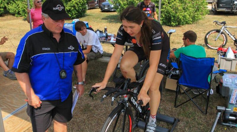 Un coach à côté d'un cycliste sur un home trainer lors d'un entrainement