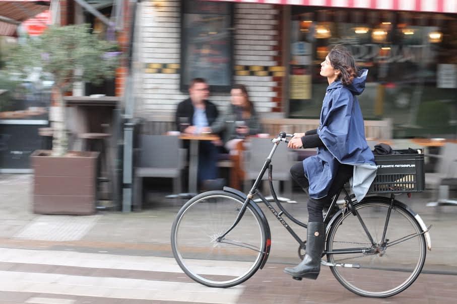 Une femme à vélo avec un poncho pour se protéger de la pluie