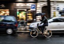 Un cycliste en vélib se protège de la pluie avec son parapluie