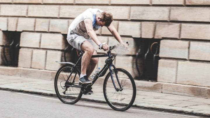 Un cycliste sur son vélo regarde sa selle
