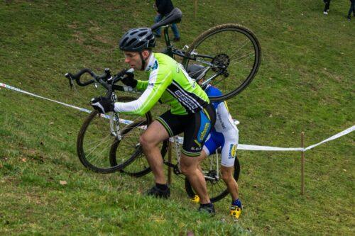 Ludo à pied avec son vélo de cyclocross sur l'épaule pour monter une pente très raide
