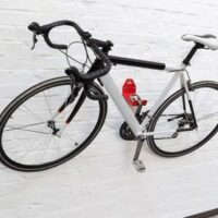 Un vélo accroché au mur par sa pédale