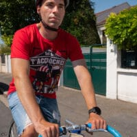 Un cycliste à vélo avec un t-shirt bio rouge Soit tu t'accroches soit tu décroches
