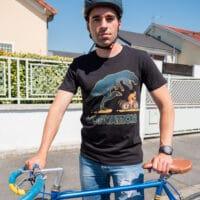 Un cycliste avec un vélo bleu et un tshirt t-rex