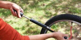 Une femme gonfle un pneu de vélo avec une pompe à main