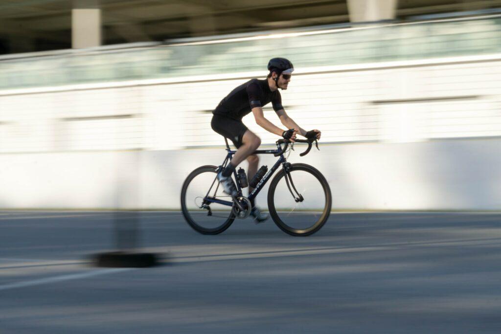 Un cycliste en tenue noire pédale sur son vélo de route rapidement