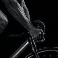 Un cycliste avec ses mains posées dans les drop du cintre de son vélo de route