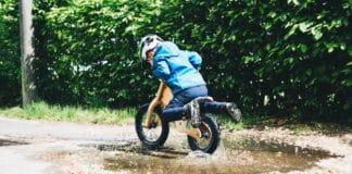 Un enfant avec une draisienne qui roule dans une flaque d'eau