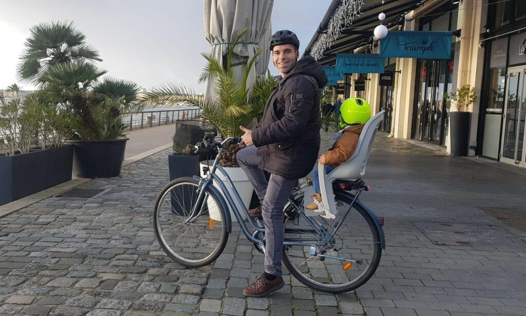 Le cycliste Ludo avec un porte bébé à l'arrière du vélo de ville Btwin