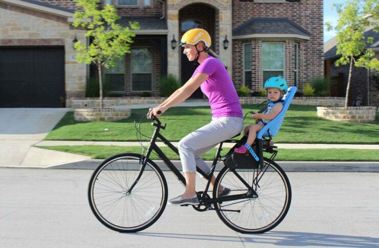 Une maman cycliste transporte un bébé à l'arrière sur son porte vélo bébé