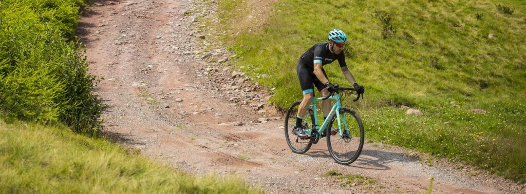 Un cycliste qui descend un chemin sur son vélo Bianchi