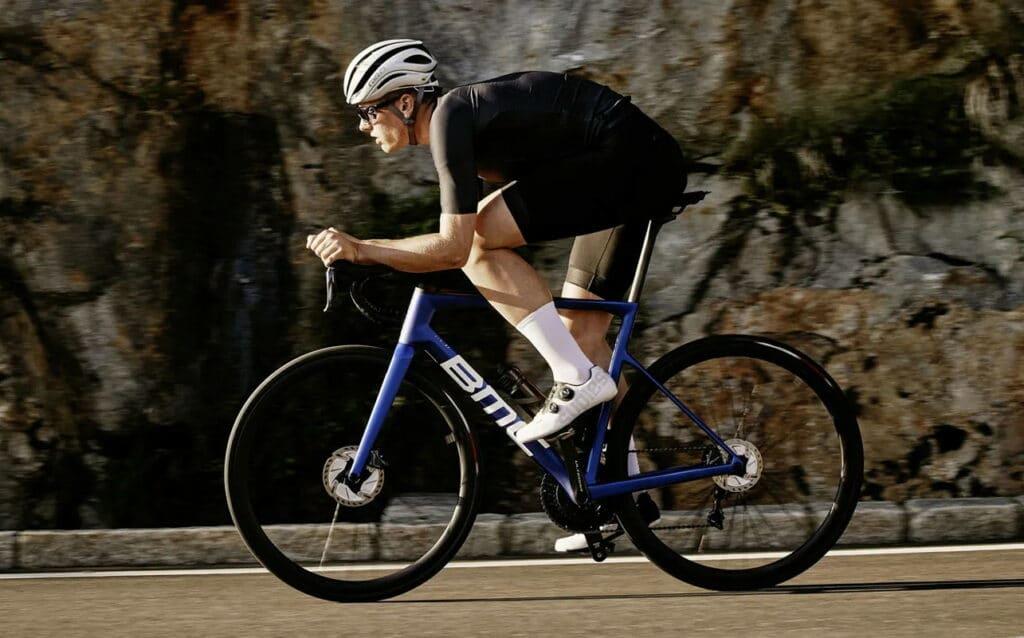 Un cycliste sur un vélo BMC TeamMachine bleu équipé de disques
