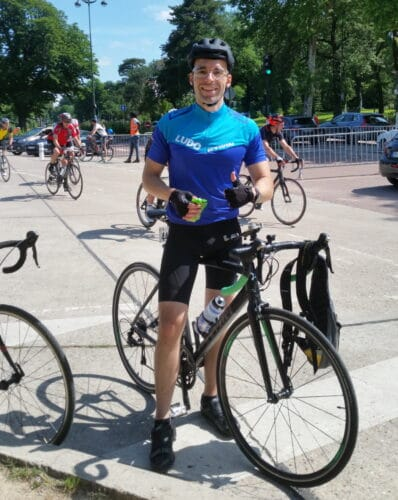 Le cycliste Ludo sur von vélo noir Btwin avec une compote dans les mains