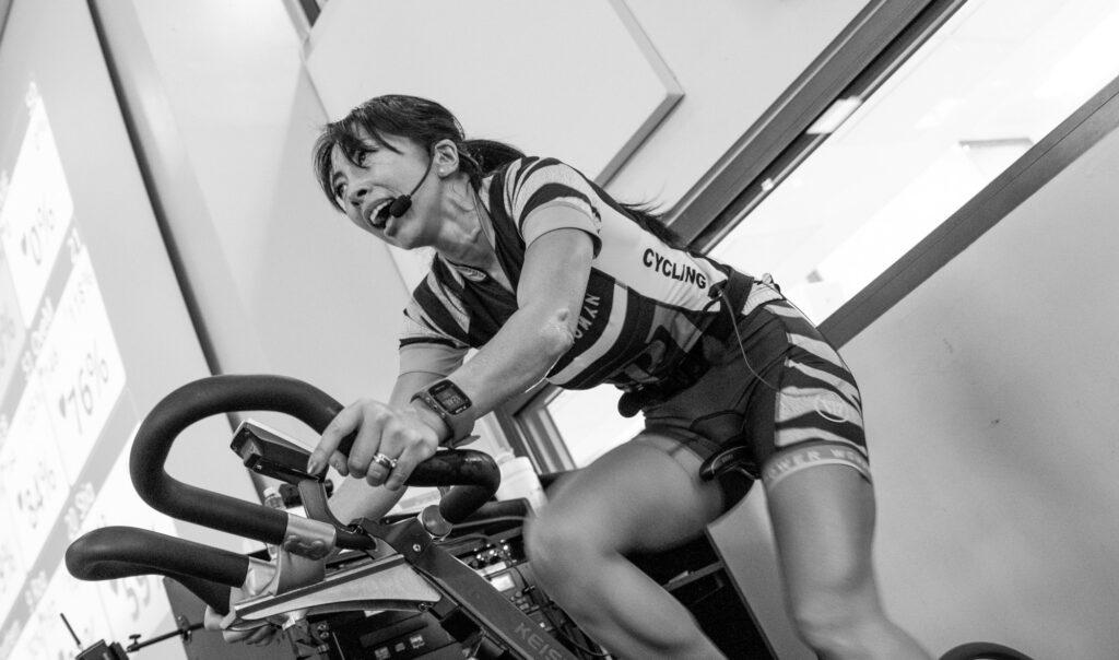Un coach féminin sur un vélo de spinning dans une salle de sport