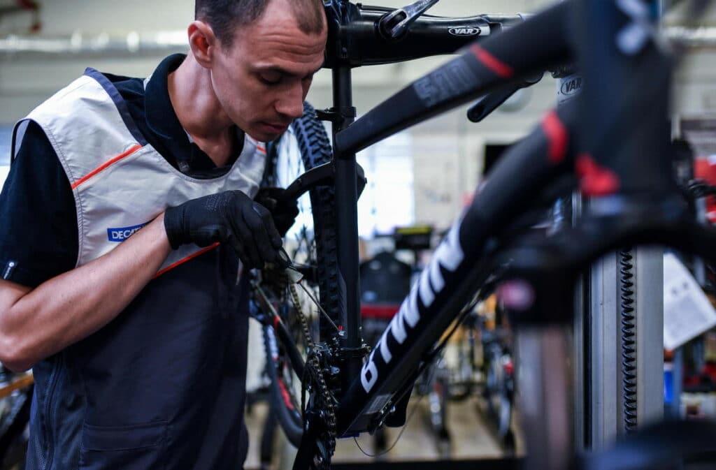 Un mécanicien qui répare un vélo dans un aterlier chez Décathlon