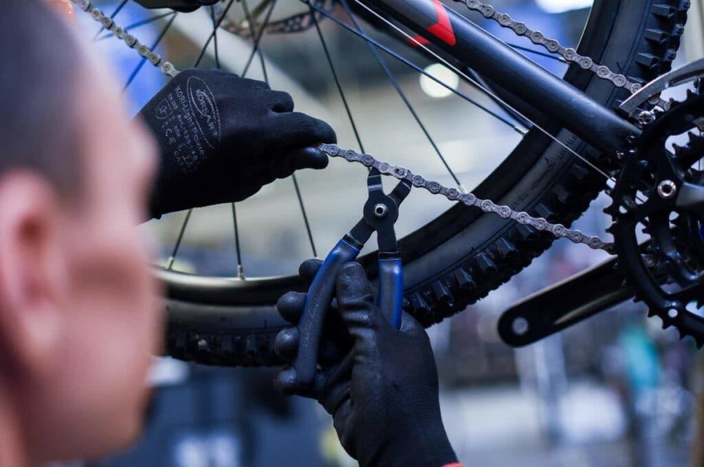 Un technicien avec un dérive chaine sur un vélo