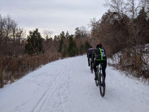 Deux cyclistes dans la neige en plein hiver