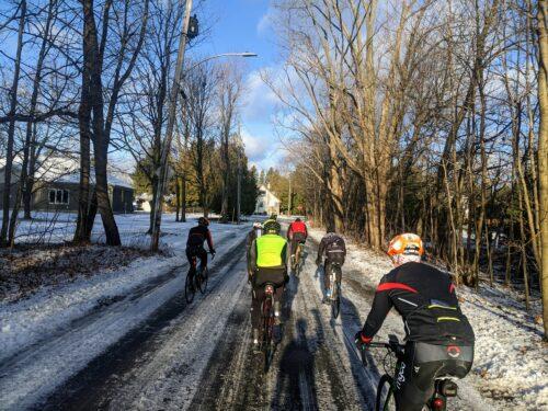 Un groupe de cyclistes qui pédalent dans le froid avec une route enneigée