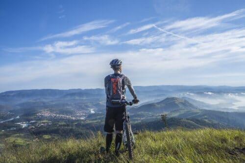 Un cycliste avec son VTT qui regarde la montagne