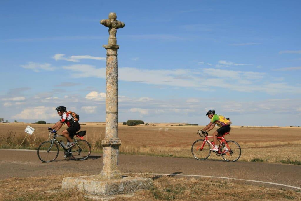 Deux cyclistes sur la route qui passent derrière une statue