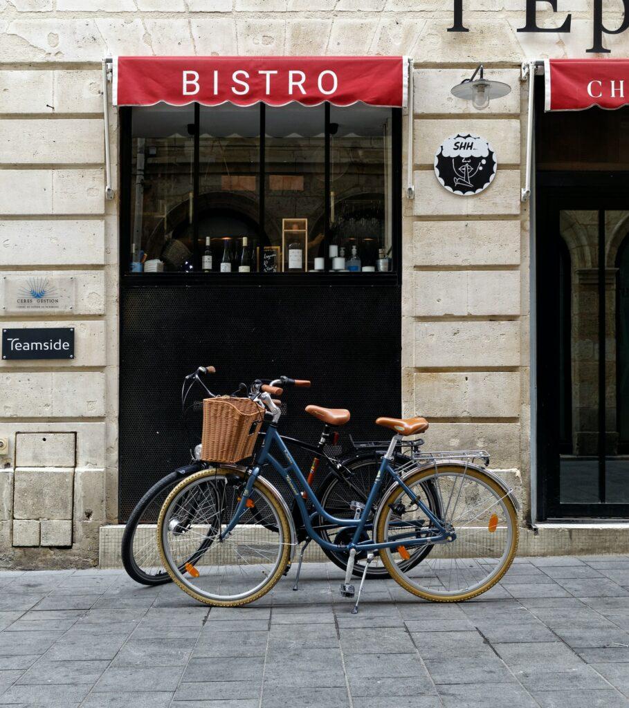Deux vélos de ville garés devant un bistrot