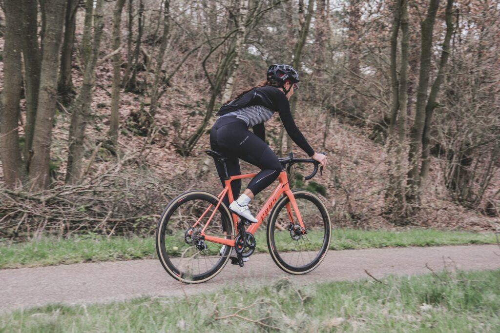 Une cycliste en sous-bois sur son vélo route