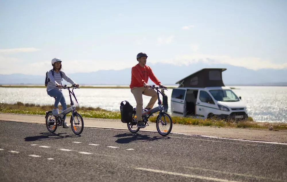 Deux cyclistes avec des vélos pliants électriques sur une piste cyclable