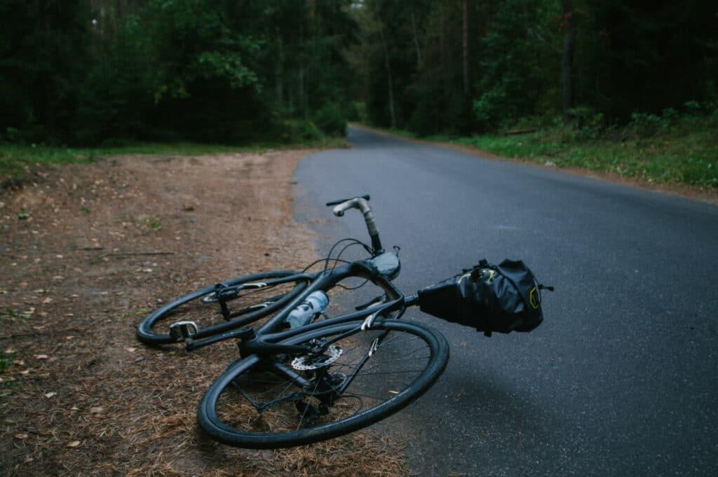 Un vélo de route posé au sol sur la route devant une forêt