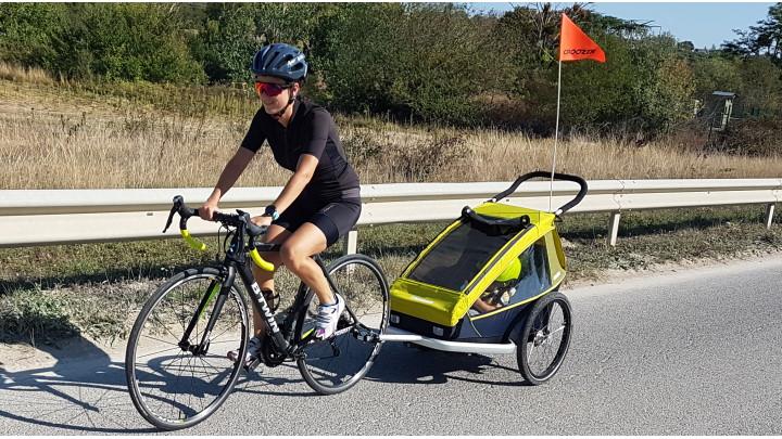 Une femme cycliste avec une remorque enfant Croozer
